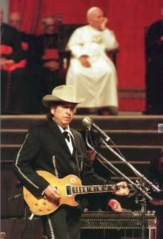 "1997 : Bob Dylan plays ""Knocking On Heaven's Door"" and ""A Hard Rain's A-Gonna Fall"" for Pope John Paul II and an audience of 200,000 at concert/mass in Bologna, Italy. For the 77 year old Pope, it was a chance to connect with young people. The pontiff invoked Dylan's song ""Blowin' In The Wind"" during his sermon"