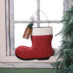"""Santa Boot Wall Pocket Primitive look Santa Boot shape wall pocket Measures approximately: 9.5 x 11 3/4 Material: Metal Glittered red and white Santa boot, with wire hanger. Metal tag that says """"Welcome"""""""