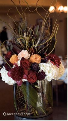 Autumn or fall centerpiece with Burgundy and pink roses, dahlias, branches, feathers, and white hydrangea Phifer Pavitt Mock Dinner Photo Shoot Orange Wedding Centerpieces, Centerpiece Decorations, Wedding Reception Decorations, Flower Centerpieces, Flower Decorations, Flower Arrangements, Wedding Ideas, Tall Centerpiece, Rustic Centerpieces