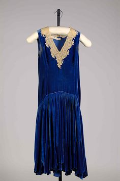 Cocktail dress by Bonnie Cashin, 1926: This flapper dress features a deep-V on a deep, velvet blue fabric. The collar is detailed with intricate lacing. I have to say, though this time period is not my favorite, I would where with design!