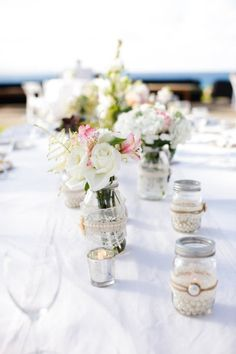 Mason jars with votives, faux pearl filler and lace/twine wraps..
