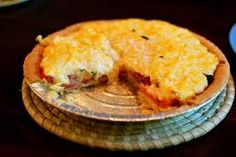 Paula Deen's Tomato Pie:  4 tomatoes, peeled and sliced/  10 fresh basil leaves, chopped/  1/2 cup chopped green onion/   prebaked deep dish pie shell/  1 cp grated mozzarella/  1 cup grated cheddar/  1 cp mayo/  Salt & pepper/   Preheat oven to 350.  Place tomatoes in a colander in the sink in one layer.  Sprinkle with salt and allow to drain for 10 min.  Layer tomato slices, basil, & onion in pie shell.  Season with s & p.  Combine cheese & mayo. Spread over tomatoes. Bake 30 min. or til…