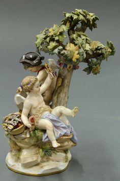 Meissen porcelain figural group, depicting a pair of putti making arrows under a tree. Highly detailed modeling of leaves and tools. Resting on a rounded base with gilt band. Marked for Meissen.