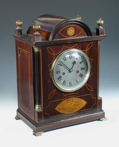 Sale F090316 Lot 686  A mahogany and inlaid mantel clock, the break arch case with four corner finials above 14.5cm (5.75in) silvered dial, with Roman numerals and twin fusee movement, quarter columns to the front angles, upon ogee feet, late 19th century h:42 w:32 cm  - Cheffins