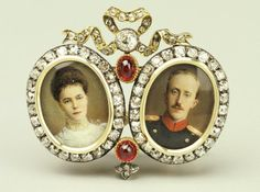 Fabergé double frame brooch, workmaster Mikhail Perchin, with a pair of oval miniatures of Peter, Duke of Oldenbourg in regimental uniform and Grand Duchess Olga, probably executed at the time of their marriage held on August 9, 1901. Mounted in gold, bordered with rose cut diamonds. Above, linking the two miniatures is a lover's knot set with rose cut diamonds, and below this one cabochon ruby. At bottom another cabochon ruby, with four small diamonds set below it, links the two miniatures.