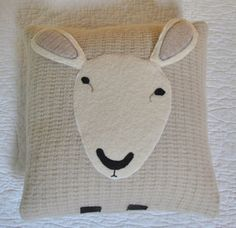 A pillow made from felted wool sweaters to resemble a sheep.