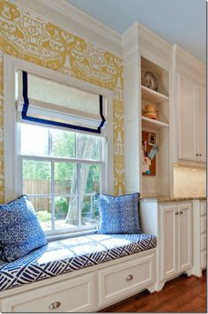 Built-in window seat in the kitchen. Love the Clarence House wall paper, roman shade with ribbon trim and tribal upholstery on the bench. Fun mix