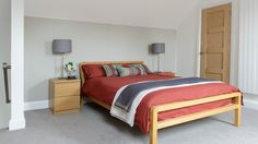 Grey wallpaper with a simple motif gives this modern bedroom a soft, slightly feminine look. Team with a neutral carpet, warm wood and a few bold colours. Here, plain scarlet bed linen lifts the scheme. Pick colours carefully - grey is versatile and works well with reds, whites and yellows