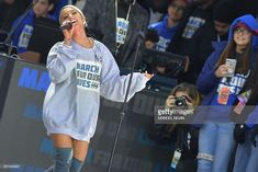 Ariana Grande singing on stage showing her bleached blond pulled back hair on stage.:).