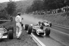 1968 — Lotus-Ford Formula One driver Jo Siffert stops to borrow a dry visor from retired teammate Graham Hill as John Surtees speeds past in his Honda during a wet French Grand Prix