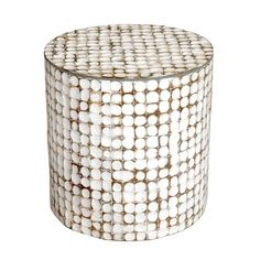 This distressed vintage accent table features a white washed finish and coconut shells that form a modern geometric design. This table offers an elegant look that would look great in any space.