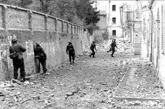 Ortona - A rifle section of Canadian troops proceeds along a narrow street, keeping close to a brick wall before crossing over to the other side. The leading soldier is carrying a Bren gun.