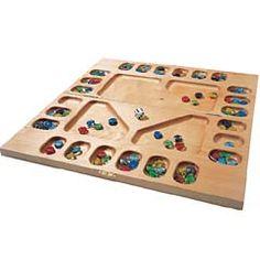 Pretty pebbles in a flat wooden board hardly look like fun, eh? Guess again. This ancient game of strategy and math is addictive.