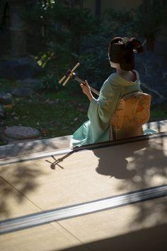 October 2016: Geiko Toshimana (Komaya Okiya) of Miyagawacho playing the shamisen in the garden of an ochaya. Source: Gaap on Photohito