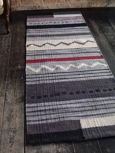 """Herbst / Winter 2013 - Der Teppich """"Uno"""" mit seinen unregelmäßigen Streifen in Schwarz-rot-grau sind ein echter Blickfang. Der Läufer ist aus strapazierfähiger Wolle gefertigt. Größte 70 x 200 cm."""