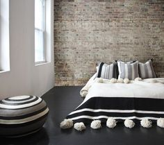 L'Aviva Home Moroccan pom-pom blanket, alpaca pillows, and Bolivian pouf   Remodelista