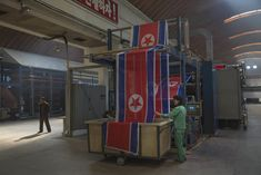 A worker guides North Korean flags into a basket at the Kim Jong-suk factory in Pyongyang.