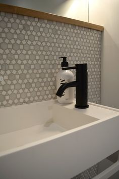 Wall hung matte white basin with black tap and geometric marble feature wall. See all the pics >>