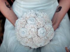 Make an unforgettable statement at your vow renewal  with an fabric flower bouquet that will never wilt and can be displayed after your big day! This design features a beguiling blend of raw-edged cotton hydrangeas and sweet rosettes. A floral offering that you will cherish.   Circumference approximately 24 inches. Lace-wrapped handle. Pearl-bead detailing.  Organic Alternative Fabric Bouquet | Green Bride Guide