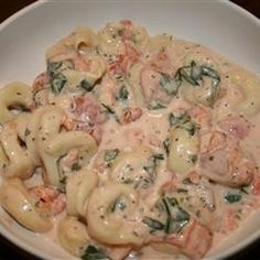 cheese tortellini served in a creamy tomato and spinach sauce.