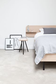 Sustainable oak bed from the brand Trecompany in collaboration with April and May and Marie Stella Maris. Graphic art and a wooden stool with black legs.