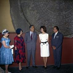 JFKWHP-KN-C22562. First Lady Jacqueline Kennedy stands in front of the Piedra del Sol (Aztec calendar, Sun Stone) during a visit to the Museo Nacional de Antropología (National Museum of Anthropology) of the Instituto Nacional de Antropología e Historia (National Institute of Anthropology and History) in Mexico City, Mexico. Left to right: Eva López Mateos; First Lady of Mexico, Eva Sámano de López Mateos; Subdirector of the Instituto Nacional de Antropología e Historia, Dr. Ignacio Bernal…