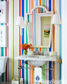 The powder room's hand-painted stripes by Deirdre Newman combine colors used throughout Rye, New York, Tudor house designed by Sara Gilbane.