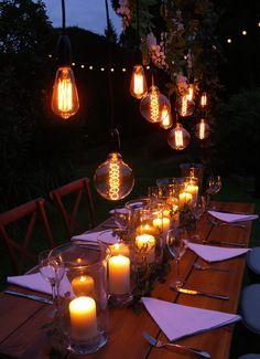 Large filament bulb festoon drops dressed with wisteria garlands over rustic table, cross back chairs, storm lanterns and ivy garlands, with battery-powered festoon backdrop. Creates a rustic and festival look. By www.stressfreehire.com #venuetransformers #stressfreerustic #stressfreefestival #stressfreelighting
