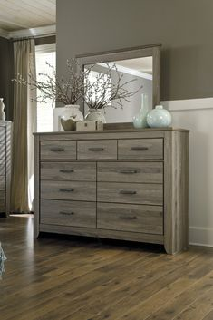 "Ashley Furniture B248-31 Zelen Dresser | JACKS WAREHOUSE The true rustic beauty of Vintage Casual style has never been brought to life more than with the warm relaxing design of the ""Zelen"" bedroom collection. The warm gray finish features a stylish white wax effect beautifully complementing the replicated oak grain all surrounding the unique horizontal pocket details and wide pilasters adorning this rustic furniture. Warm gray sophisticated vintage finish with white wax effect over…"