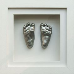 Silver painted plaster cast baby feet in a white box frame