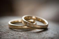 Et par vielsesringe i guld, med sten i brudens ring.