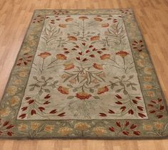 Large area rug with touches of greens, reds, golds, grays, blue-grays
