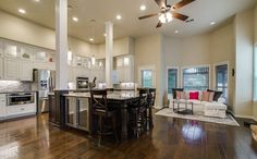 Open kitchen with wood pillars, mahogany island, white cabinets and large dining island