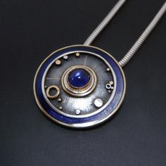 Circles pendant by Abi Cochran (2cm diameter). Silver, 22ct and 18ct gold, iolite and translucent resin...
