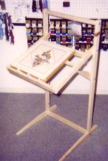 """Philip Floor Stand  Ideal for use with stretcher bars, scroll frames, or embroidery hoops    Overall Height: 39.5""""  Overall Width: 21.5""""  """"Easel"""" size: 20"""" wide x 18.5"""" deep    Predrilled holes to position """"easel"""" at 3 different heights  Adjusts to 3 different angles  Leather scissors holder can be mounted on right or left side    Project threads may be hung on the top bar  Top bar is flat so that a lamp may be clamped onto it"""