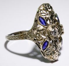 Lot 127: 18k White Gold, Blue Spinel and Diamond Ring; Art Deco filigree setting having a round cut central diamond adorned by four marquis cut spinels; marked 18k inside band