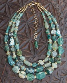 """Ran - Norse Sea Goddess. Displaying the most wondrous shades of green and blue, this one of a kind necklace features ancient glass fragment beads excavated in Afghanistan. Also referred to as Roman Glass, these beads are estimated at 800 to 2000 years old and have a beautiful iridescent patina which is enhanced by a sprinkling of hand faceted aquamarine beads together with the 22k gold-plated sterling silver beads, clasp and extender. Finished length: 23.5"""" adjustable to 28""""."""