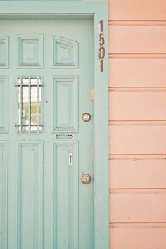 Pastel teal door on a pastel peach pink home