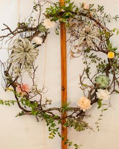 A springy wreath of branches, air plants, succulents, vines, and fresh blooms