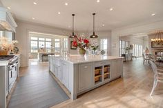 Large kitchen with farmhouse pendants and inset cabinets