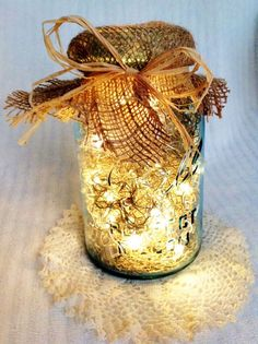 Tiny lights inside a mason jar with a burlap top - pretty for an outdoor table centerpiece