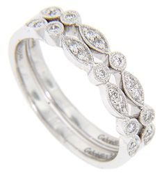 These antique style 14K white gold stackable wedding bands have approximately .10 carats total weight of diamonds set in a delicate pointed oval and circle pattern. The bands are photographed here with R1830 (sold separately). Size: 7. We can re-size. The bands are frequently purchased as a set for $1,100.00 but they are also available individually for