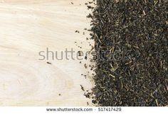 green tea leaves on wooden table. over light