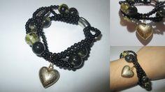 Pulseira elástica de missangas pretas e pérolas douradas. Com pendente dourado em formato de coração. Tamanho: 17cm. Peça manufaturada.  Referência: OM021