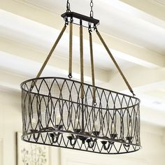 The Denley Pendant Chandelier. Ten swooped candle arms are surrounded with an oval geometric wire mesh shade for layer upon layer of rich visual depth.