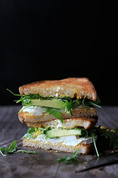 goat cheese and avocado sandwich with rucola and mustard.