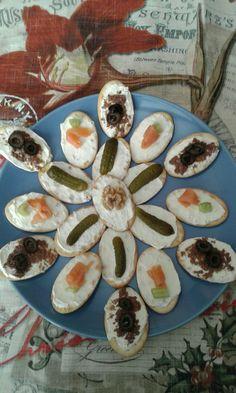Cracker all'acqua con crema al formaggio, cetriolini e salmone affumicato e paté di olive