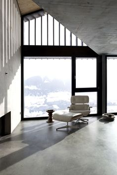 A white Eames Lounge Chair & Ottoman; beyond, through the window, snow-capped Swiss mountains. Concrete floors, walls, and ceilings complete this austere interior. Haus in Morissen by Hurst Song.