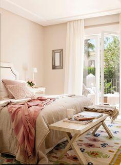 Dormitorios con ropa de cama en tonalidades rosa, banqueta de madera, alfombra y amplio ventanal