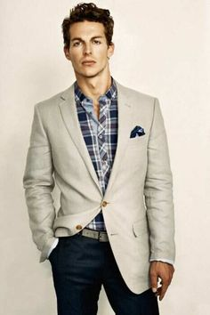 Mens street style fashion: blue white checkered shirt, navy blue pants jeans, beige cream coloured blazer jacket, pocket square